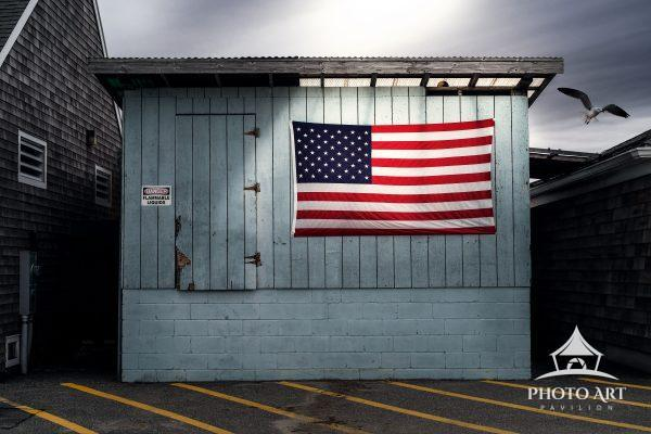 Bright American flag on the side of a cool old building, let up by interesting light. Color