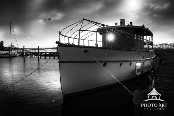 Old historic fishing boat with the setting sun shining through a window. Black and white photograph.