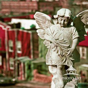 Statue of an angel in Green-Wood Cemetery, with a background of Brooklyn rowhouses