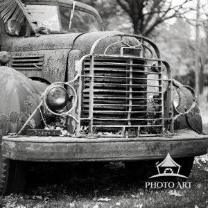 Old truck along the roadside, left to decay. Black and white photograph.