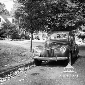 Old car parked along a street in a typical neighborhood... with an old time feel. Black and white