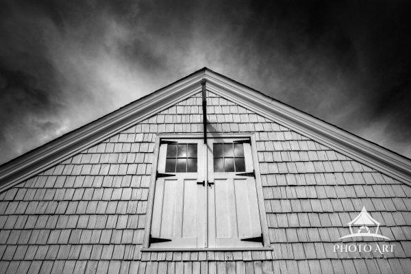 Old bard, with doors on the second story, against a dramatic and cloudy sky. Black and white