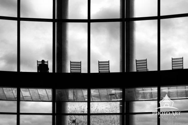 Interesting building and windows, with chairs along the balcony and a single person sitting and