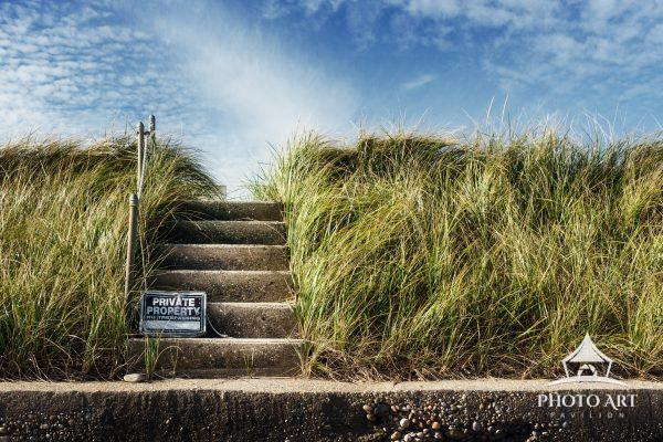 Steps to the beach surrounded by tall beach grass, along a private area roadway on the North Shore