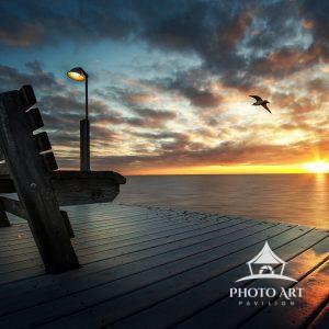 Bench and light facing the water as the sun sets over the Great South Bay in Sayville, NY. Suffolk