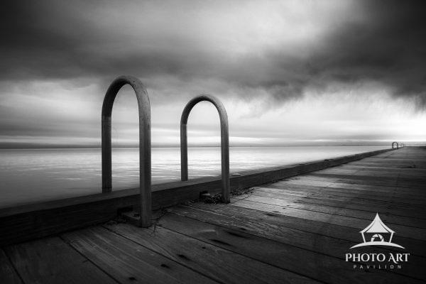 Long old pier under interesting storm clouds at the marina near East Islip, New York. Ladder depends