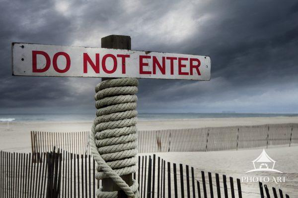 Do Not Enter -- A sign warning people to stay off the beach, amongst the dune fences and empty