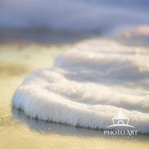 Close up of foam meeting the shoreline at Island Beach State Park, New Jersey in winter.