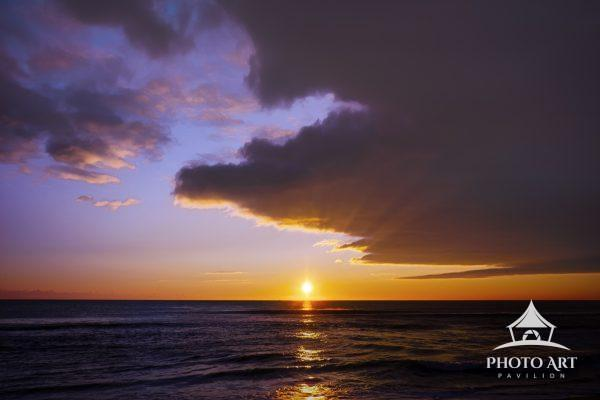 Sun rises over the horizon causing sun rays against clouds on the beach at Island Beach State Park,