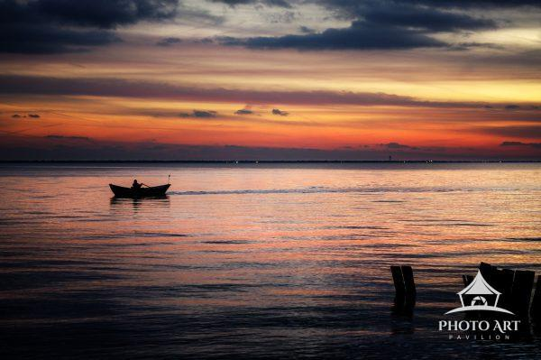 Lone man rowing in a boat along the Great South Bay at sunset. Long Island, NY near Sayville. Color
