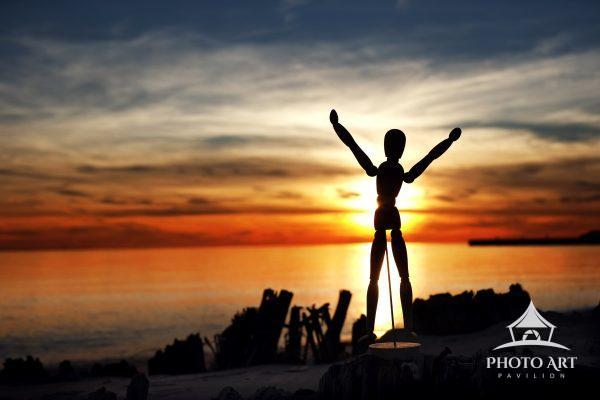 Little wooden figure / man stands in victory as the sun sets over the Great South Bay. Long Island,