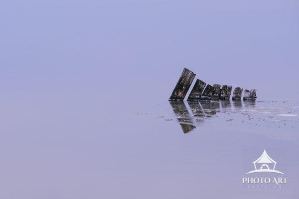 Little bits of an old dock stick up from the frozen ice and cold water of The Great South Bay on a