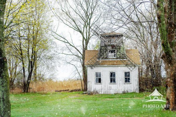 An amazing old windmill on a snowy down, near the east end farms of Long Island, New York. Color