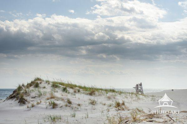 Dune along the shores of Fire Island, with a lifeguard chair and couple walking in the background.