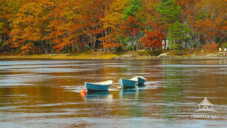 The lush colors of autumn leaves accentuate this lakeside view, as boats are at rest upon the water