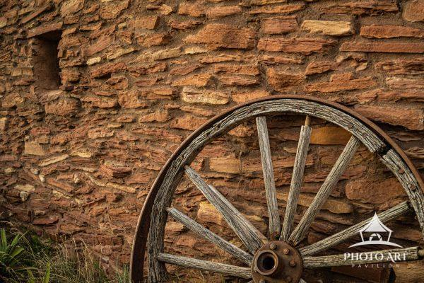An old wagon wheel resting on a stone wall