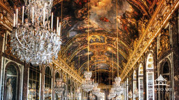 The ornate painted ceiling and chandeliers in the Hall of Mirrors at Versailles, France.