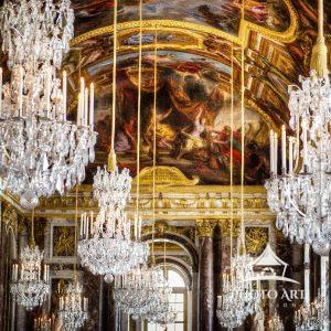 Chandeliers hanging from the painted ceiling in the Hall of Mirrors at Versailles, France.