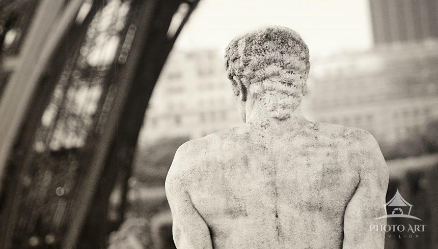 """A statue from """"behind"""" looking out toward the Eiffel Tower in Paris, France."""
