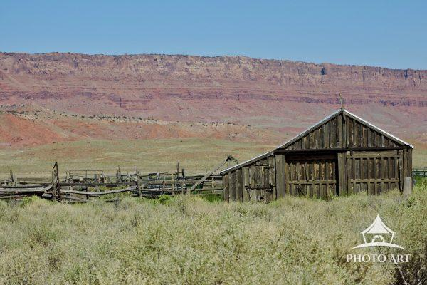 A barn sits in front of the vibrant Vermillion Cliffs in Arizona