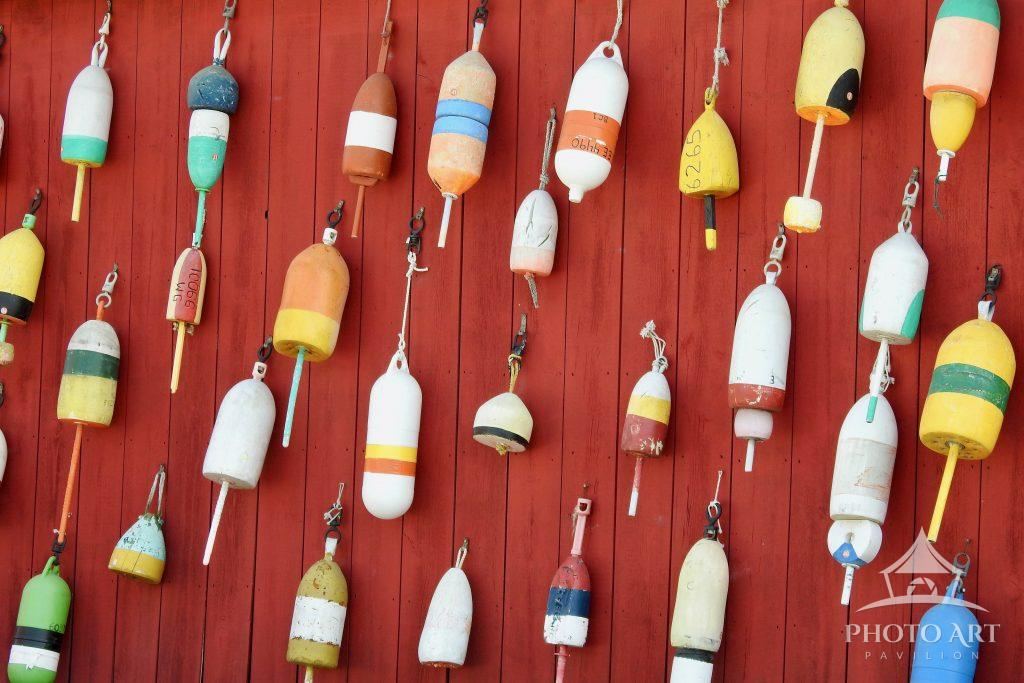 Lobster Pot Markers hang on a bright red wall, somewhere in Maine!
