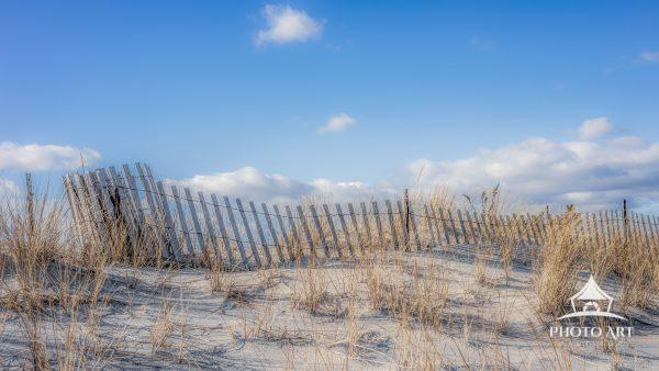 A typical wood fence atop a Fire Island dune on a bright, sunny day. The bluest of skies contrast
