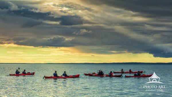 Kayakers on Skilak Lake in Kenai Fjords National Park, Alaska, take in the golden sunset as the sun
