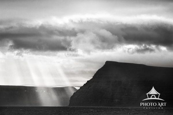Dramatic sunrise scene with sun rays against mountain cliffs in Iceland.