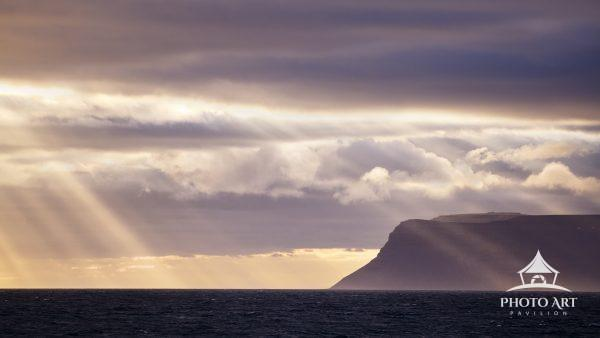 Amazing sun rays over the ocean and against the dramatic landscape of Iceland.
