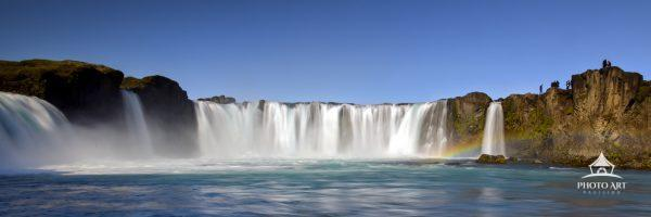 Extreme panorama of the main part of Godafoss Falls in Iceland on a beautiful blue sky day.