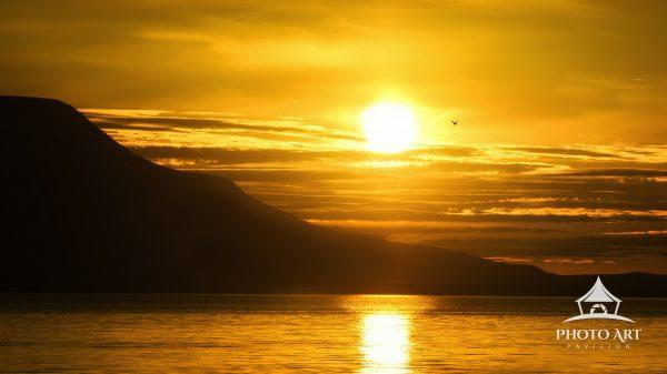 Golden sun setting against the mountains at midnight at Akureyri, Iceland.
