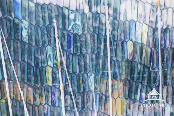 Impressionistic close up of the Harpa Concert hall in Reykjavik, Iceland with salis of boats in