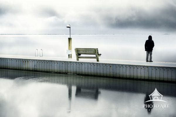 Personal standing on the pier, near a bench and a light, looking out onto the Great South Bay on a