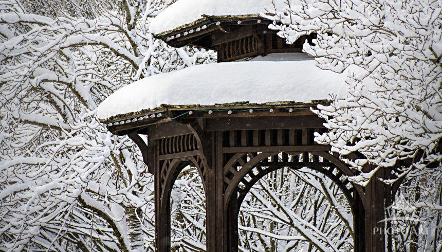 A wooden gazebo or pavilion covered and surrounded by fresh fallen snow in Downingtown,