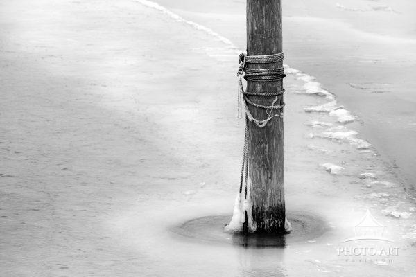 Single poll in an empty and cold marina along the south shore of Long Island. The bay is starting to