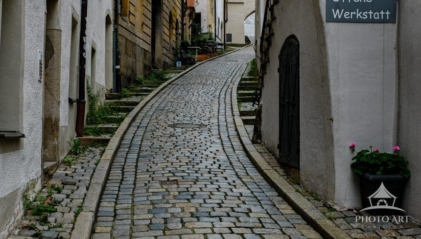 A narrow street hides an entrance to an artisans collective not far from the three rivers of Passau,