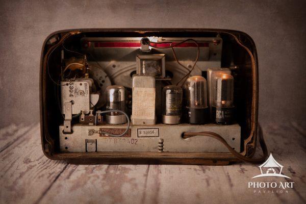 The open back of a vintage bakelite radio exposes glowing radio tubes