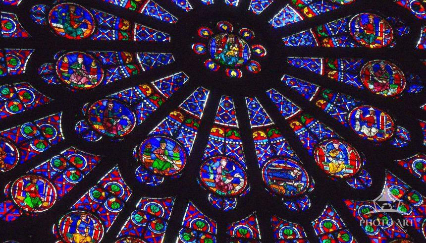 The large front stained glass window of Notre Dame. Brilliant colors from the inside.