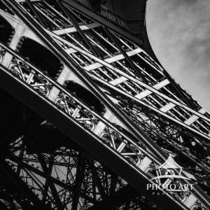 An up close black and white abstract view looking up at the Eiffel Tower.