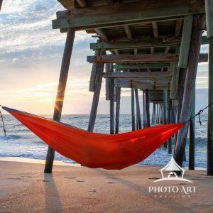 A couple shares the sunrise in a hammock under the Avon pier.