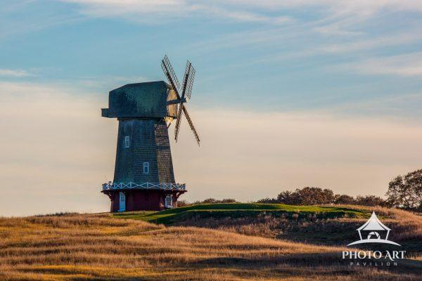 Very large windmill set on a golf course.