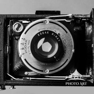 The lens and aperture of a Kodak folding camera is the subject of this still life black and white