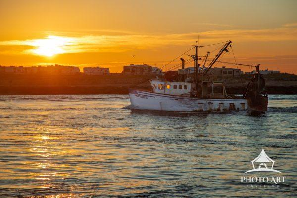 A commercial fishing boat returning weighed down at sunrise.