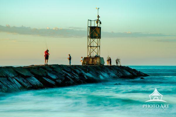 Time exposure of fisherman (motion blur) with waves in foreground.