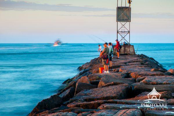 Early rising fishermen along rock jetty, commercial fishing boat returning in distance.