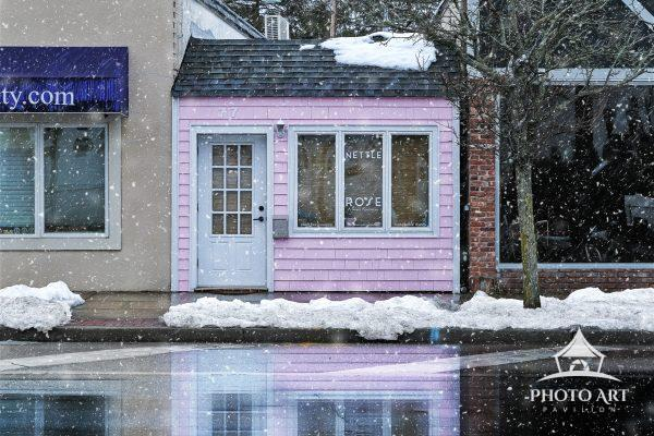 Little pink storefront and its reflection in the snow, along Main Street. Color photograph.