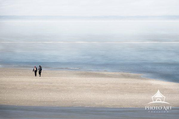Two friends walk along a sand bar on the North Shore of Long Island, on a foggy day. Long Island