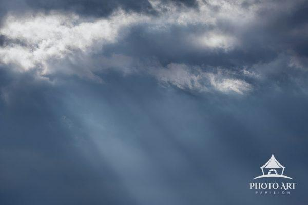 Dark blue sky with sun rays streaming through the clouds at Marsh Creek park, Pennsylvania.