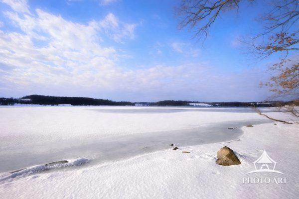 Snow and ice on Marsh Creek lake against bright blue sky in March in Pennsylvania.