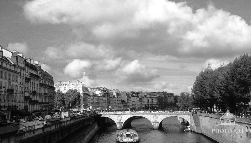 Clouds sweep the sky, making way for sunlight over the Seine, the iconic river that flows through